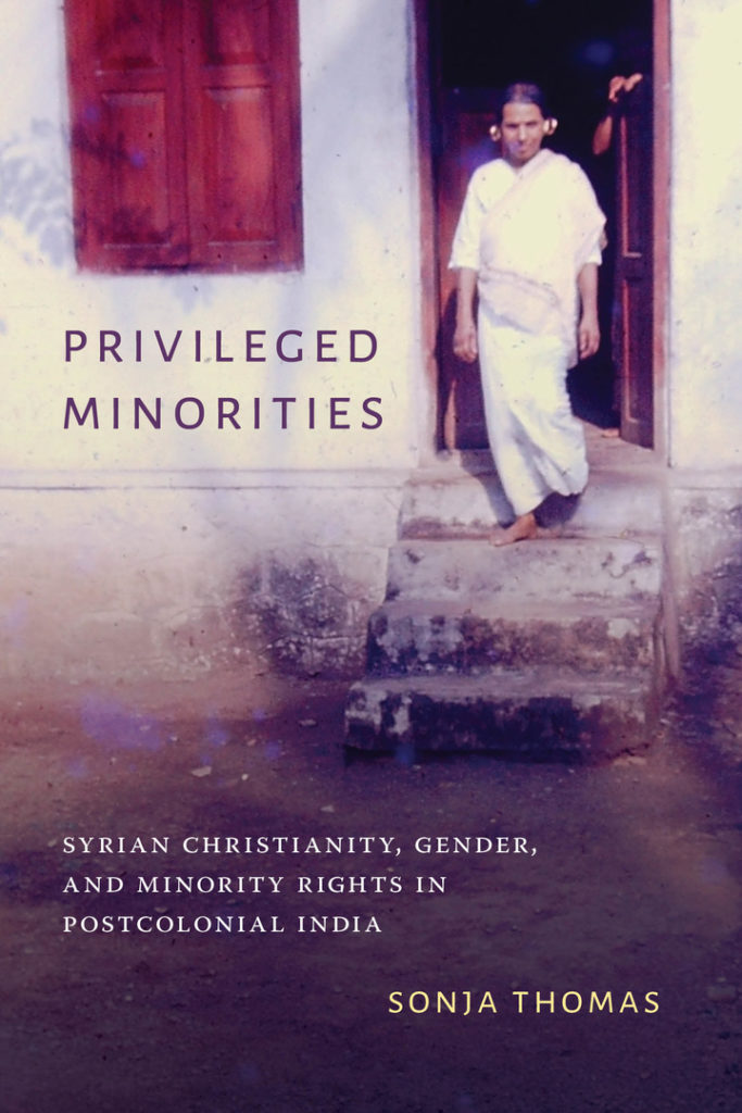 "Book cover image: In the background, a person clad in traditional white Syrian Christian clothing, with gold rings on their ears, stands on the steps before the door of a house, a closed window to their left. In the foreground, there is the title, ""Privileged Minorities,"" the subtitle, ""Syrian Christianity, gender and minority rights in postcolonial India,"" and the author's name, ""Sonja Thomas."""