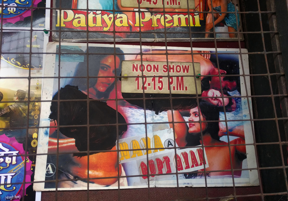 A photograph of a movie poster. The title, 'Naya Gupt Gyan' is displayed along with images of two semi-clothed women, as well as a man and a woman embracing. For one of the women, the upper body is blacked out.