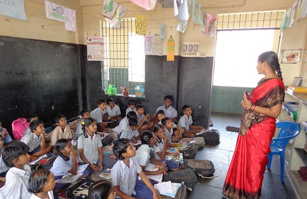 A standing woman in a red sari teaches rows of young uniformed children seated on the floor in a primary school classroom in India.