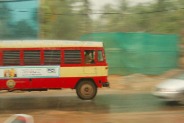 A panning shot of a KSRTC bus moving from left to right. A smaller car, blurred, is seen coming from the right to left, veering away from the bus. It is a rainy day, and some construction site can be seen on the other side, behind the two vehicles.