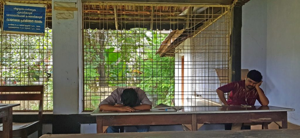 Scene from a reading room in Thrissur district, central Kerala Sign on the top left reads: 'Maintain silence, Do not smoke, Do not use mobile phones.' Two men sit at benches, one with his head down on the desk, another staring at a mobile device on the bench, with earphones on.