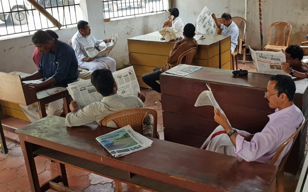 A photograph of a reading room in Kerala, where seven men sit around at benches, reading newspapers.