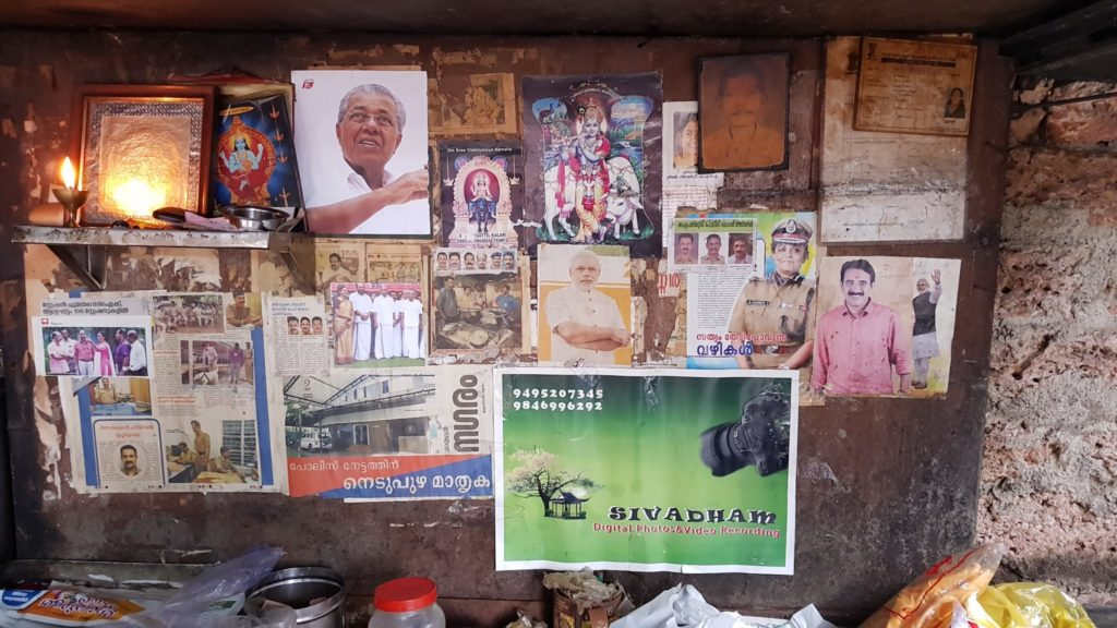 A Collage of paper clippings, politician images and hindu idols on a wall.