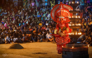 An image of the theyyam performance. A large crowd is seen off focus, in the background. In focus, towards the foreground, is the theyyam, left of frame. Also in focus, in front of the theyyam is a large lit lamp.
