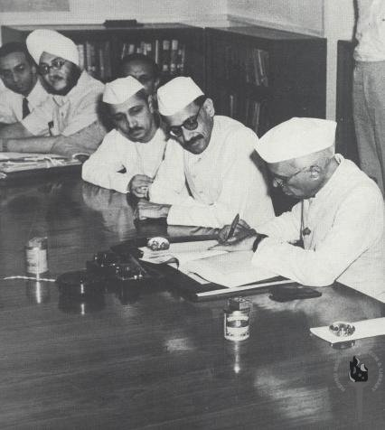 Nehru signing the FYP (right), as five others look on, seated to his right in the image. K.N. Raj seen at the far end of the table.