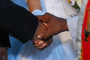 image of the close-up of a priest holding the hands of a newly married couple.