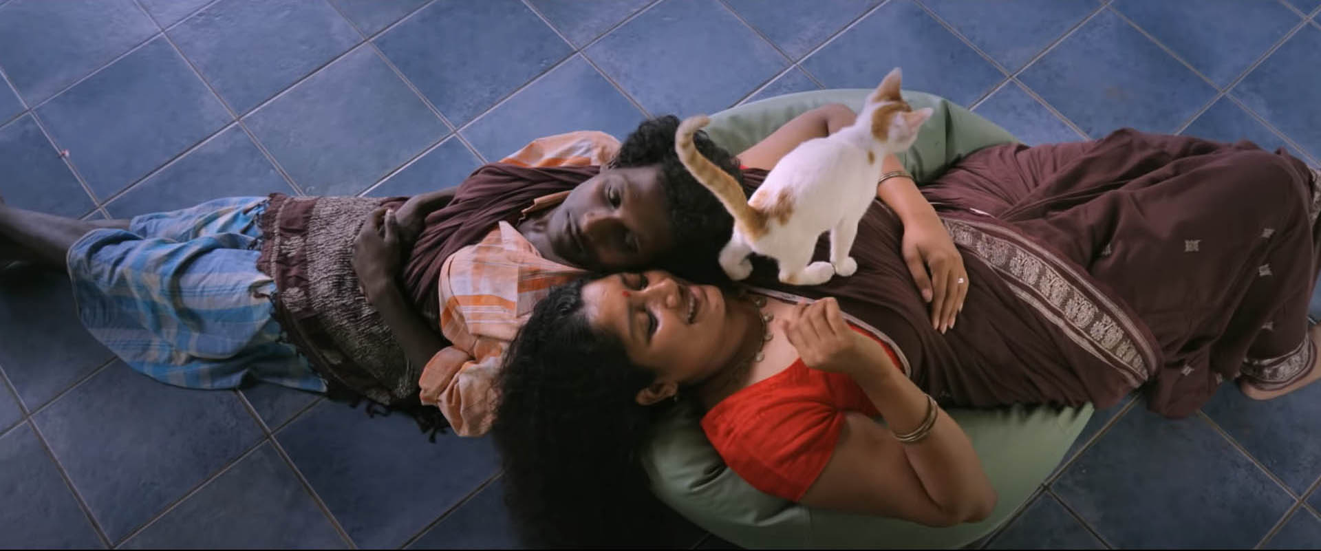 Top-angle shot of Gulikan and Dancer--two characters form the film--lying on a beanbag with their heads next to each other, stretched out in opposite directions, with a cat standing on the Dancer's chest