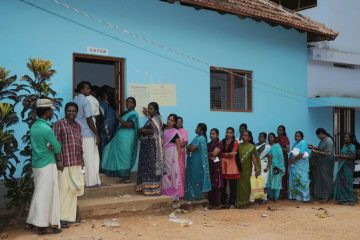A queue of people waiting to get into a polling book. Women queuing to the right, men to the left.