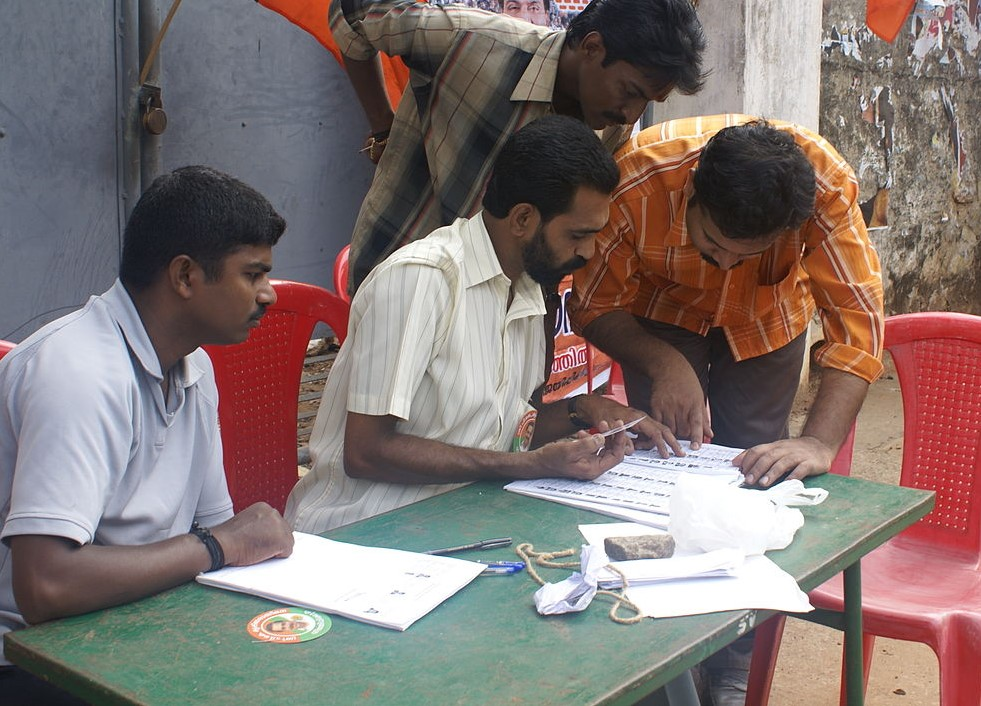 Four men look up a voter list at a table.