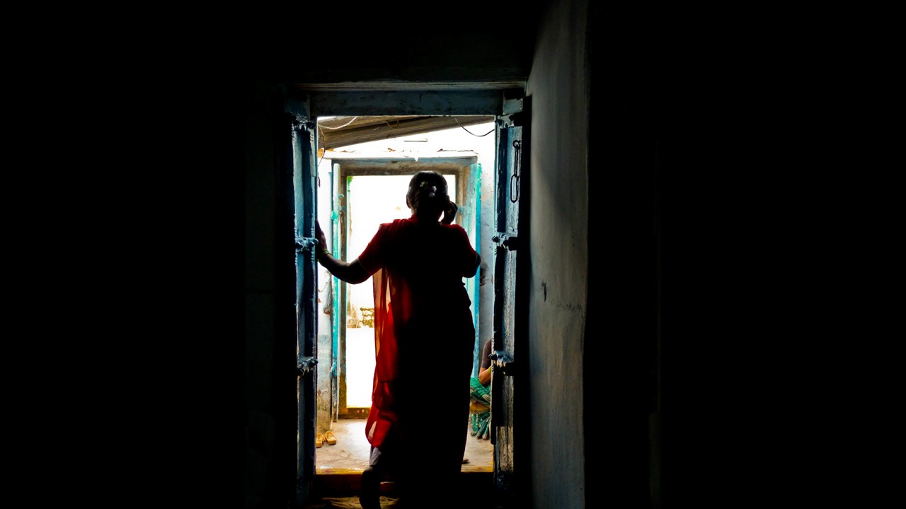 A silhouette of a woman standing near a door, her hands resting on the frame of the door to her left; she faces away from the camera